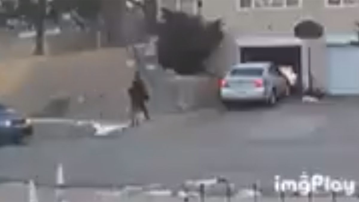 A surveillance camera watches as a thief steals an unattended car warming-up in the driveway.