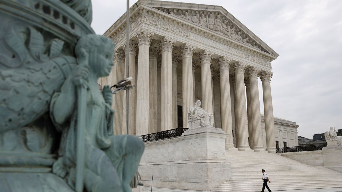 A police officer walks outside the Supreme Court on Capitol Hill in Washington, Monday, July...