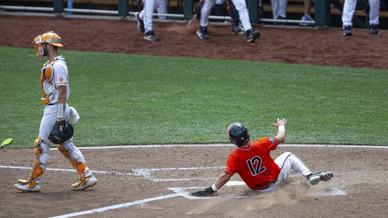Virginia's Logan Michaels (12) slides home for a run against Tennessee in the seventh inning...