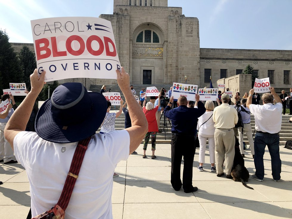 Supporters hold up signs as State Sen. Carol Blood announces her run for governor on Monday,...