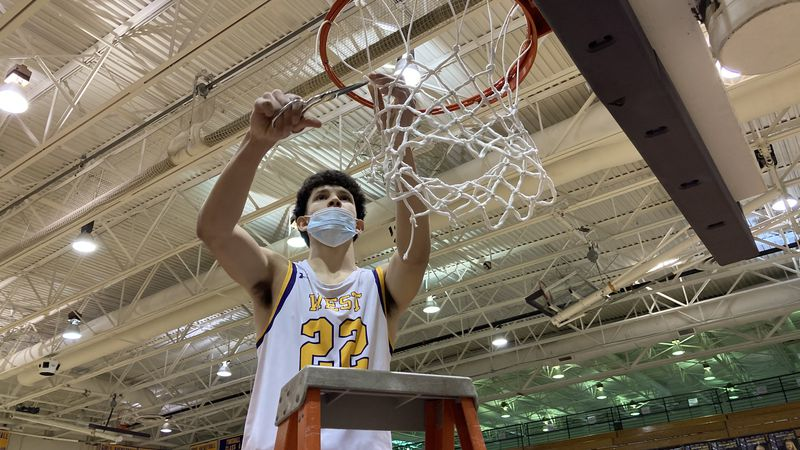 Josiah Dotzler cuts down a net for Bellevue West