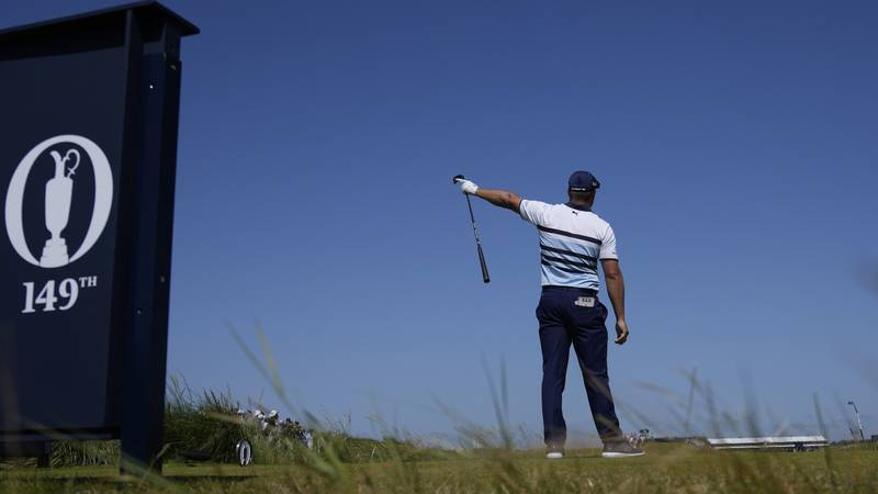 United States' Bryson DeChambeau gestures as his ball goes left from the tee after his drive...