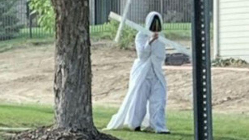 Person in costume walks neighborhood.