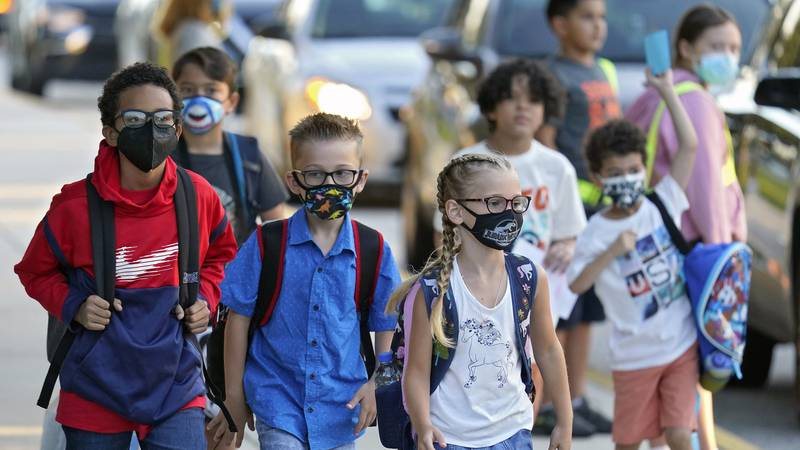In this Tuesday, Aug. 10, 2021 file photo, Students, some wearing protective masks, arrive for...