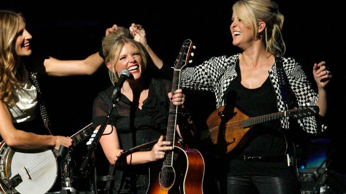 FILE - In this Oct. 18, 2007 file photo, Emily Robison, left, and Martie Maguire, right, adjust Natalie Maines' hair as the Dixie Chicks perform at the new Nokia Theatre in Los Angeles. The Grammy-winning country group have dropped the word dixie from their name and are now going by The Chicks. The move follows a decision by country group Lady Antebellum to change to Lady A after acknowledging the word's association to slavery. (Source: AP Photo/Gus Ruelas, File)