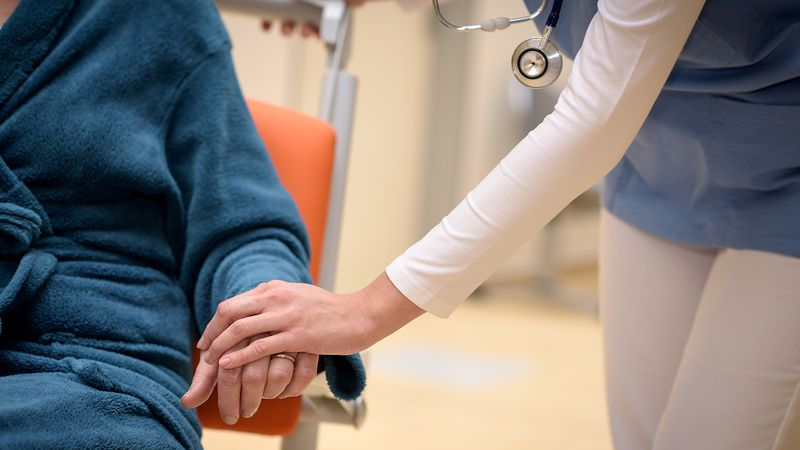Close-up of doctor holding senior patient hand sitting in wheelchair