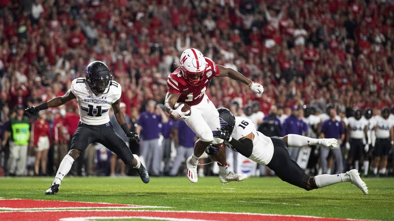 Nebraska's Rahmir Johnson (14) dives into the end zone to score a touchdown ahead of...
