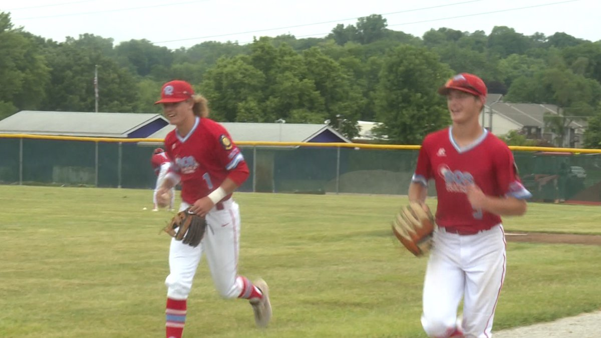 Ralston's Nolan Sailors and Kaleb Holm run back to the opposing dugout at Bellevue East High...