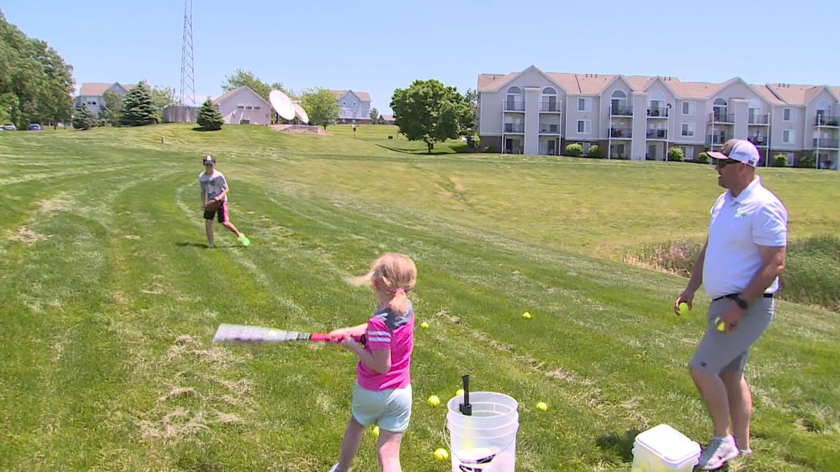 The Melcher family practices hitting balls off of a tee outside their apartment in Elkhorn on Sunday, 5/31/20. (Rex Smith)